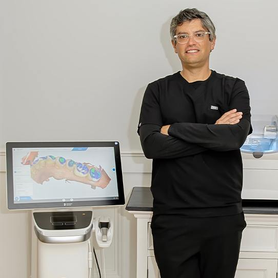 Doctor Graber standing next to CEREC system