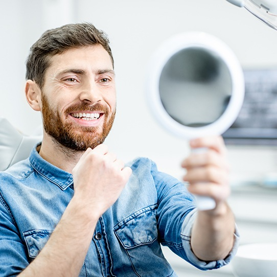 Man looking at smile in mirror during dental treatment
