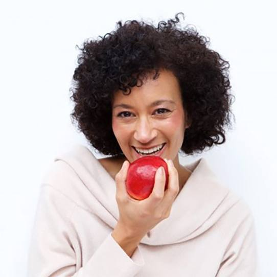 smiling woman taking a bite into a red apple