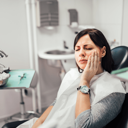 Woman holding checking during emergency dental visit