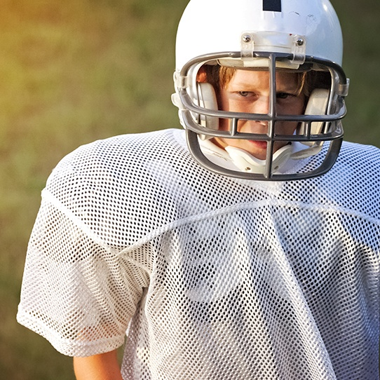 Teen boy wearing football helmet and athletic mouthguard