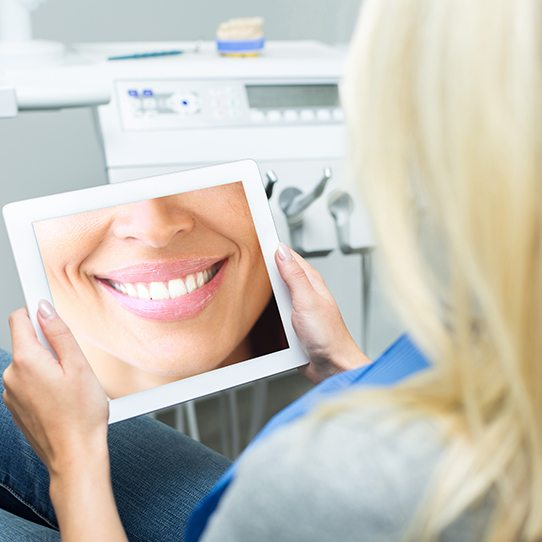 Woman looking at virtual smile design on computer screen
