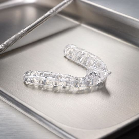 Clear nightguard for bruxism treatment on metal tray