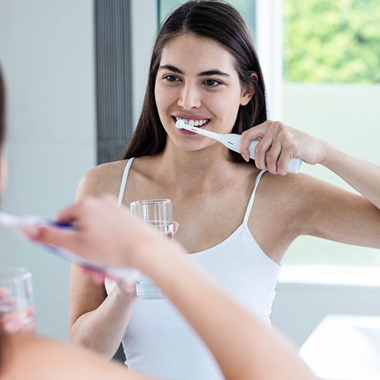 Woman brushing teeth at home