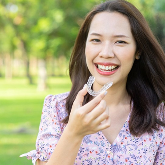 Smiling woman outside holding Invisalign in Shelton