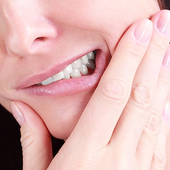 Woman in need of root canal holding jaw