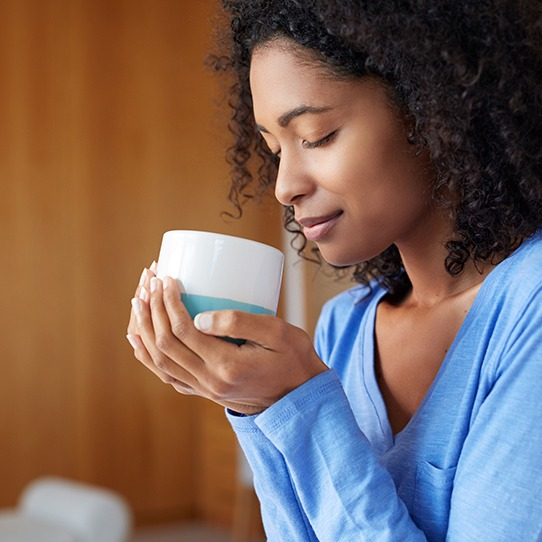 Woman drinking a cup of coffee which can cause tooth staining