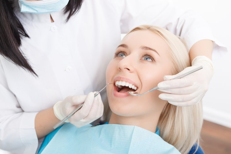A young woman having her teeth checked during a regular dental exam